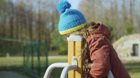 Cute little girl in blue hat playing on the playground. Female turning on the carousel and smiling. Carefree childhood. stock video