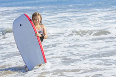 Cute little girl boarding in the ocean. A cute little girl playing in the ocean during her summer vacation Royalty Free Stock Images