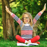 Cute little girl with a book in a green summer park with hands r Royalty Free Stock Photo