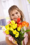 Cute little girl with bouquet of flowers smiling Stock Images