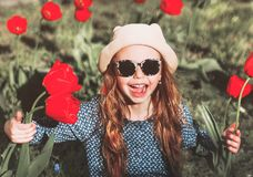 Cute little girl with a bouquet of spring tulips. Cute little girl with a bouquet of red spring tulips royalty free stock images