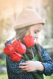 Cute little girl with a bouquet of spring tulips. Cute little girl with a bouquet of red spring tulips stock images