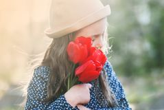 Cute little girl with a bouquet of spring tulips. Cute little girl with a bouquet of red spring tulips royalty free stock photos