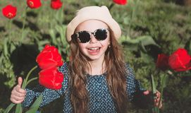 Cute little girl with a bouquet of spring tulips. Cute little girl with a bouquet of red spring tulips royalty free stock photo