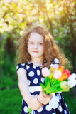 Cute little girl with bouquet of tulips on green spring backgrou Stock Image