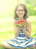 Cute little girl with bowl full of fresh strawberries.  Pre - teen girl with glasses and teeth - dental  braces.  Stock Image