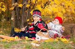 Cute little girl and boy eating bagels in autumn park. Stock Images