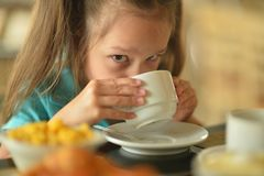 Cute little girl at breakfast Stock Photos