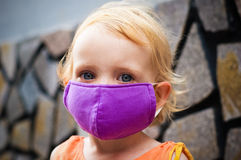 Cute little girl in bright face mask Royalty Free Stock Photo