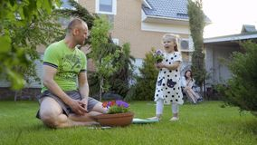 Cute little girl bring pot with flowers to her father stock footage