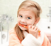 Cute little girl brushing teeth in bath Stock Photo