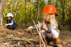 Cute Little Girl Building A Wooden Tepee Royalty Free Stock Photography