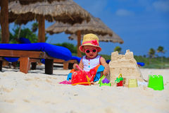 Cute little girl building sandcastle on the beach Stock Images