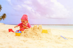Cute little girl building sandcastle on beach Royalty Free Stock Image