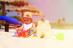 Cute little girl building sandcastle on beach Stock Photo