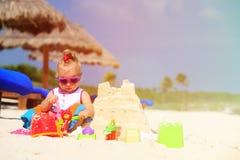 Cute little girl building sandcastle on beach Stock Photography