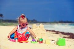 Cute little girl building sandcastle on beach Stock Image