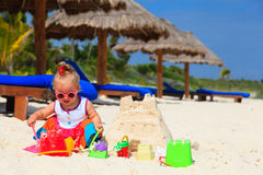Cute little girl building sandcastle on summer Stock Images