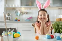 Cute little girl with bunny ears headband and painted Easter eggs sitting at table in kitchen royalty free stock photos