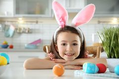 Cute little girl with bunny ears headband and painted Easter eggs sitting at table in kitchen