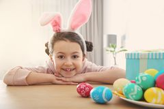 Cute little girl with bunny ears headband and painted Easter eggs sitting at table royalty free stock photos
