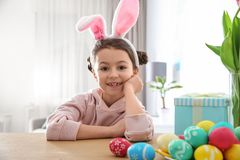 Cute little girl with bunny ears headband and painted Easter eggs sitting at table stock photo