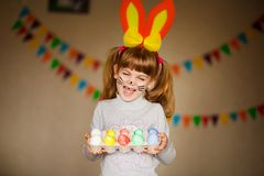 Cute little girl with bunny ears holding bright Easter egg royalty free stock image