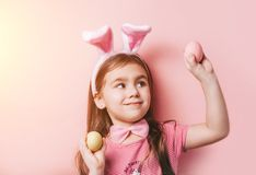 Cute little girl with bunny ears on pink background. Easter child portrait, funny emotions, surprise. Copyspace for text stock photography