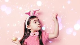 Cute little girl with bunny ears on pink background. Easter child portrait, funny emotions, surprise. Copyspace for text royalty free stock photos