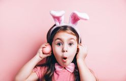 Cute little girl with bunny ears on pink background. Easter child portrait, funny emotions, surprise. Copyspace for text stock images
