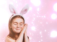 Cute little girl with bunny ears on pink background. Easter child portrait, funny emotions, surprise. Copyspace for text royalty free stock photography