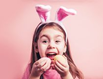 Cute little girl with bunny ears on pink background. Easter child portrait, funny emotions, surprise. Copyspace for text stock photo