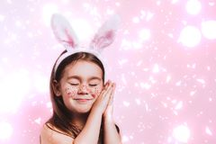 Cute little girl with bunny ears on pink background. Easter child portrait, funny emotions, surprise. Copyspace for text stock image