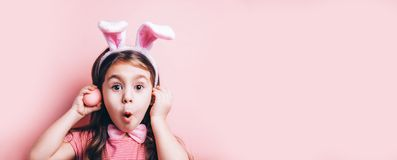 Cute little girl with bunny ears on pink background. Easter child portrait, funny emotions, surprise. Copyspace for text stock photos
