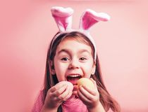 Cute little girl with bunny ears on pink background. Easter girl portrait. Cute little girl with bunny ears on pink background. Easter child portrait, funny royalty free stock image