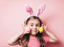 Cute little girl with bunny ears on pink background. Easter girl portrait. Cute little girl with bunny ears on pink background. Easter child portrait, funny royalty free stock photos