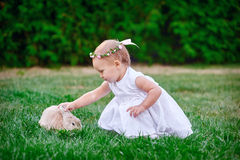 Cute little girl with a bunny rabbit has a easter at green grass Stock Photo