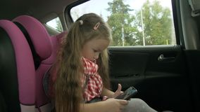 Cute little girl busy with smart phone while sitting in the back seat of the car. Lovely elementary age child playing on. Cellphone during road trip 4K stock footage