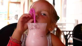 Cute little girl in cafe with milkshake cocktail stock video