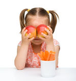 Cute little girl with carrot and apples Stock Photography