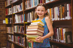 Cute little girl carrying books in library Stock Image
