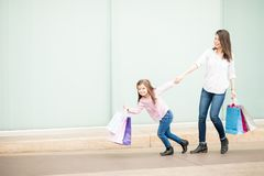 Fed up little girl pulling mother out off a shopping center. Cute little girl carrying shopping bags pulling mother outside shopping mall Royalty Free Stock Images
