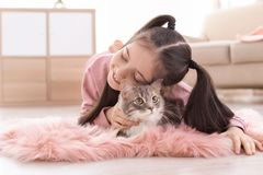 Cute little girl with cat lying on floor royalty free stock photography