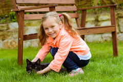 Cute little girl with cat. Outdoor Royalty Free Stock Image