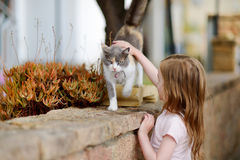 Cute little girl and a cat outdoors. On hot summer day in Italy Royalty Free Stock Photos