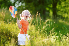 Cute little girl catching butterflies and bugs with her scoop-net Stock Photo