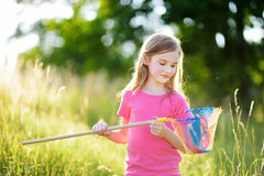 Cute little girl catching butterflies and bugs with her scoop-net Stock Images