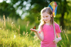 Cute little girl catching butterflies and bugs with her scoop-net Royalty Free Stock Photos