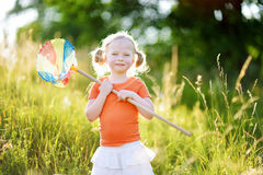 Cute little girl catching butterflies and bugs with her scoop-net Stock Image