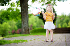 Cute little girl catching butterflies with a scoop-net Stock Image